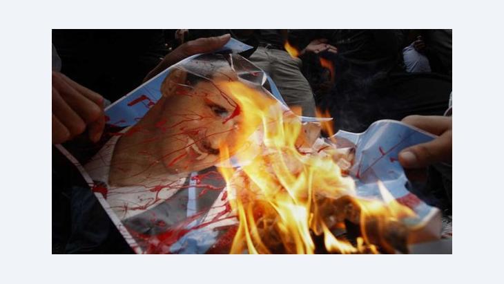 Demonstranten verbrennen ein Plakat ihres Präsidenten Baschar al-Assad vor der Syrischen Botschaft in Nicosia; dapd