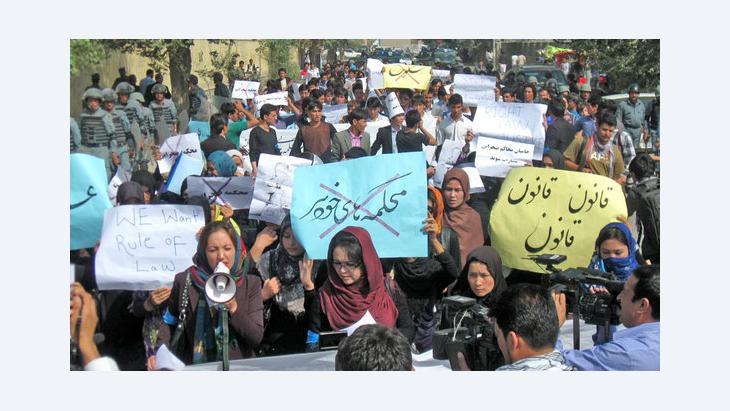 Männer und Frauen demonstrieren unter Polizeischutz in Kabul am 24. September 2012 gegen Gewalt gegen Frauen; Foto: Hossain Sirat/DW
