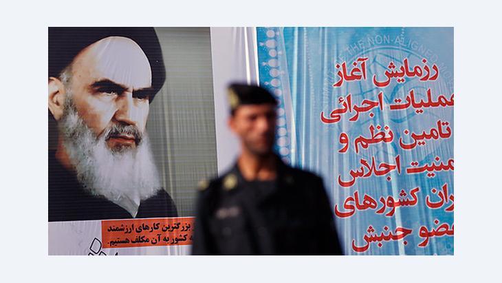 Polizist vor einem Plakat mit dem Bild Ayatollah Khomeinis in Teheran; Foto: mehrnews