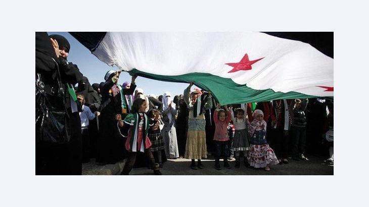 Syrische Aktivisten bei einer Anti-Assad Demonstration unter einer riesigen Flagge vor der syrischen Botschaft in Jordanien; Foto: AP/Mohammad Hannon