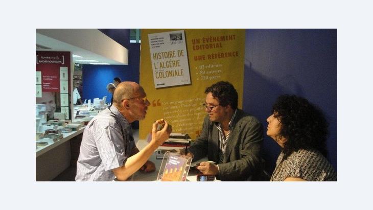 Der algerische Schriftsteller Amin Zaoui (rechts) diskutiert mit einem Leser an einem Stand auf der Buchmessse in Algier; Foto: Martina Sabra