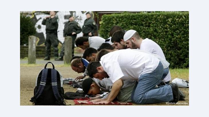 Salafisten beten in einer Fußgängerzone in Deutschland; Foto: dpa/picture-alliance