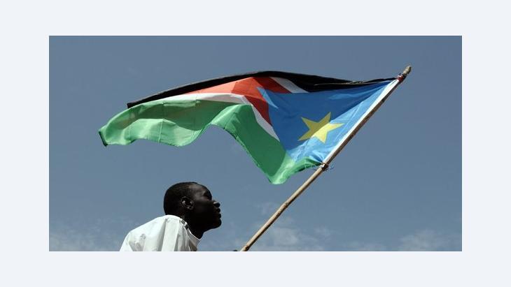 Mann hält Flagge Südsudans; Foto: picture-alliance/dpa