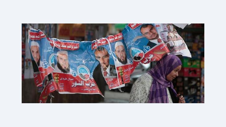 Ägypterin passiert aufgehängte Wahlplakate mit Kandidaten der islamistischen Al-Nour-Partei; Foto: AP/dapd