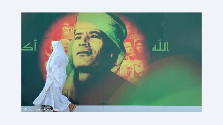Verschleierte Frau läuft vor einem Gaddafi-Plakat; Foto: dpa