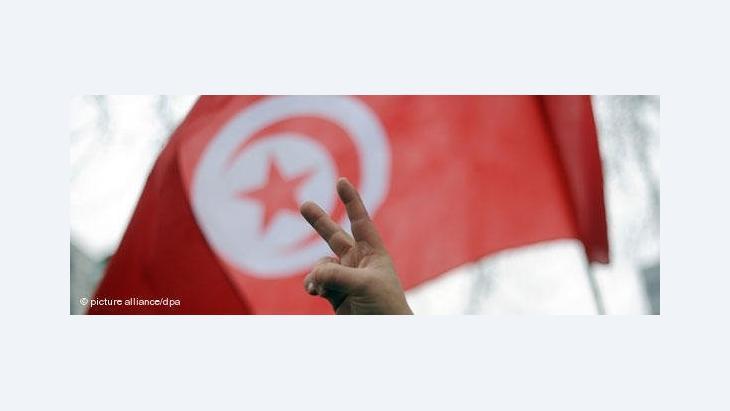 Demonstrant zeigt vor tunesischer Nationalfahne das Victory-Zeichen; Foto: dpa