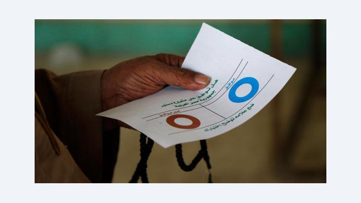 Ägypter hält bei der Stimmabgabe zum Referendum einen Wahlzettel; Foto: dapd