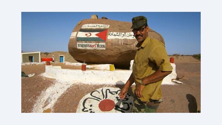 Ein Mann steht vor einem Grenzstein in Bir Lehlu, einer von der Frente Polisariao kontrollierten Stadt in der Westsahara; Foto: DW/Karlos Zurutuza
