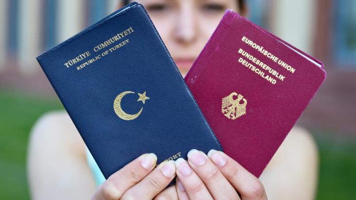 Eine junge Studentin hält ihren deutschen und türkischen Pass hoch.
