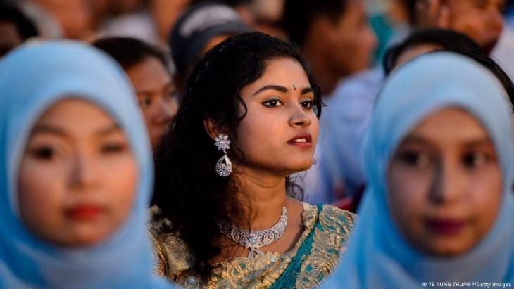 Ein Hindu-Mädchen und muslimische Mädchen nehmen an einer interreligiösen Gebetszeremonie für den Frieden teil.