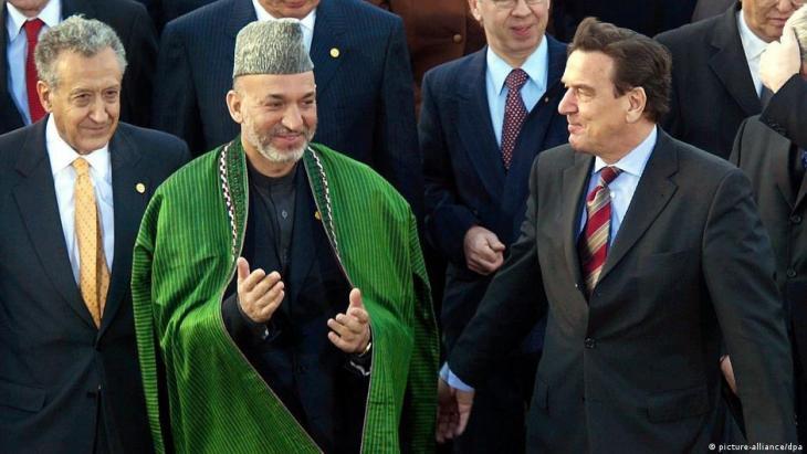 """Petersberg bei Bonn, der UN-Sondergesandte für Afghanistan Lakhdar Brahimi, der afghanische  Präsident Hamid Karzai und der damalige Bundeskanzler Gerhard Schröder (von links nach rechts) stehen für ein """"Familienfoto"""" zusammen am 2. Dezember 2002 zum Beginn der internationalen Afghanistankonferenz (Foto: picture-alliance/dpa)"""