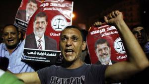 """Anhänger der Muslimbruderschaft tragen auf einer Demonstration Plakate mit dem Foto von Präsident Mursi und der Aufschrift """"Das Volk will den Aufbruch""""; Foto: AP"""
