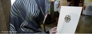 Muslima mit Kopftuch in Deutschland liest Auszüge aus einem Gesetzestext; Foto: dpa