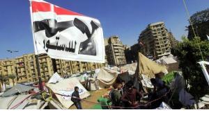 Auf dem Tahrirplatz sitzen Mursi-Gegner vor ihren Zelten, über ihnen eine Fahne mit der Aufschrift ''Nein zur Verfassung'', 10. Dezember 2012; Foto: Reuters