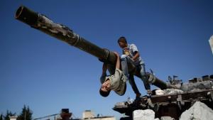 Kinder auf einem zerstörten syrischen Panzer in Aleppo; Foto: AP/Muhammed Muheisen