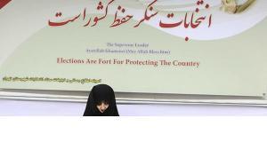 Verschleierte Frau vor Plakat mit Wahlempfehlungen Khameneis; Quelle: Mehr