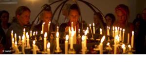 Menschen zünden Kerzen für die Opfer in Norwegen; Foto:Matt Dunham/AP/dapd