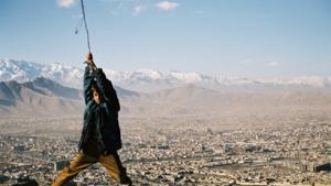 Auf einem der Berge im Zentrum von Kabul lassen sich Kinder an einem alten Stahlseil baumeln, das von einem Mast herabhängt. Im Hintergrund der Kessel von Kabul mit einem Teil der Stadtfläche. Mittlerweile leben geschätzte vier Millionen Einwohner in der Hauptstadt. Strom und Infrastruktur kommen mit dem Bevölkerungswachstum nicht nach.