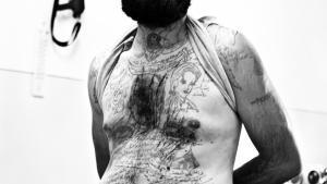"""Wie die heilige Dreieinigkeit hat sich ein Bäckergehilfe die Familie Assad auf seine Brust tätowiert. In der Mitte Hafiz al-Assad links darunter dessen verstorbener Sohn Basil und rechts daneben der amtierende Präsident Baschar al-Assad. Als die Rebellen Aleppo eingenommen haben, hat der Bäckergehilfe sich ihnen ergeben, die Gesichter mit einem Rasiermesser aus dem Körper geritzt und gerufen """"Ich gebe mein Blut für die Freie Syrische Armee."""" Vermutlich weniger aus Überzeugung als aus Angst vor d"""