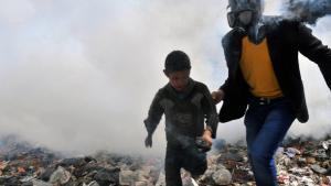 In Aleppo zieht ein Mann ein Kind aus einer Kampfhandlung; Foto: Getty Images/AFP