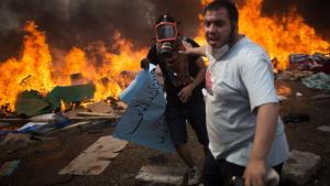 Mursi-Anhänger fliehen vor der Gewalteskalation in Kairo, im Hintergrund Flammen; Foto: dpa/AP
