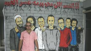 Ahmed Maher steht im Büro der Protestbewegung 6. April in Gizeh. Das Graffito zeigt verschiedene 'Märtyrer der Revolution', allen voran Khaled Said (Mitte); Foto: © Markus Symank