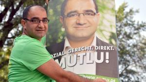 Der Direktkandidat des Bündnis 90/Die Grünen für Berlin-Mitte, Özcan Mutlu, hängt in Berlin Wahlplakate auf; Foto: Britta Pedersen/dpa