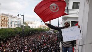 Mann hält tunesische Flagge und Plakat mit der Aufschrift: Ben Ali, hau' ab!, Tunis, 2011; Foto: picture-alliance/dpa