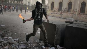 Demonstrant und Gegner der neuen Regierung in Kairo wirft Molotowcocktail auf Sicherheitskräfte in Kairo; Foto: dpa/picture-alliance