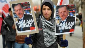 """Gegner der AKP-Regierung hält Plakat mit dem Porträt-Bild Erdogans und der Aufschrift """"Starker Dieb""""; Foto: Reuters"""