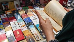 Iranerin liest ein Buch an einem Büchertisch in Teheran; Foto: Shabestan.ir