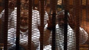 Der Chef der Muslimbruderschaft, Mohammed Badie (r.), und ein weiteres Mitglied der Muslimbruderschaft eingesperrt in einem Käfig während des Prozesses gegen die Muslimbrüder in Kairo; Foto: dpa/picture-alliance