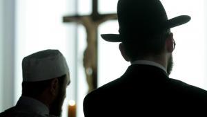Angehöriger der muslimischen und jüdischen Konfession vor einem Kreuz in einer Kirche; Foto: Getty Images