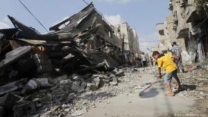 Palästinensischer Junge kehrt mit einem Besen in den Trümmern zerstörter Häsuer in Gaza; Foto: AFP/Getty Images