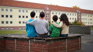 Eine syrische Familie sitzt vor einem Asylwohnheim der Zentralen Ausländerbehörde des Landes Brandenburg; Foto: dpa/picture-alliance