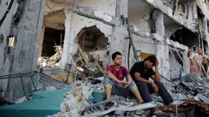 Zwei junge Männer sitzen auf den Schuttbergen ihres zerstörten Hauses im Viertel Shajaiyeh in Gaza-Stadt; Foto: Reuters