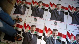 Mann steht auf Wahlplakaten des syrischen Präsidenten Baschar al-Assad; Foto: Phil Moore/AFP/Getty Images