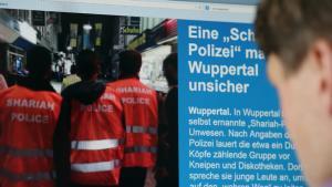 """Ein Mann schaut am 05.09.2014 in Köln auf die Berichterstattung über die """"Scharia-Polizei"""" im Internet; Foto: Oliver Berg/dpa"""