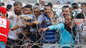 Syrische Flüchtlinge erhalten Wasser von Mitarbeitern des türkischen Roten Halbmondes; Foto: Reuters/Murad Sez