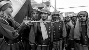 """Schauspieler der Nachstellung der Schlacht von Kerbela finden sich vor Beginn der Aufführung hinter der Bühne zusammen. Diese Männer spielen die Rollen der sunnitischen Ummayaden, die gegen die Armee Husseins kämpften und ihn schließlich töteten. Mit der Hinrichtungsgeste spielen sie ironisch auf die sunnitischen IS-Kämpfer (""""Daesh"""") an, die mit dem Köpfen von Geiseln und gegnerischen Kämpfern die Region heute in Schrecken versetzen."""