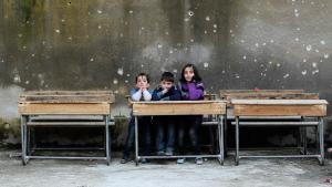 Syrische Kinder in einem mit Einschusslöchern übersäten Schulraum in Aleppo; Foto: Reuters/Muzaffar Salman