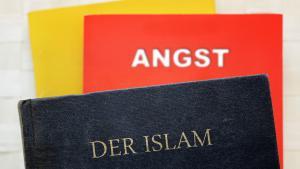 Symbolbild - Bücher in deutschen Nationalfarben, Islam und Angst; Foto: Imago/Christian Ohde