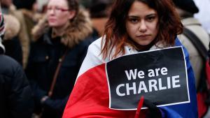 """Eine junge Frau aus Liverpool mit der französischen Trikolore hät ein Schild mit der Aufschrift """"We are Charlie""""während einer Gedenkveranstaltung für die Opfer von Paris; Foto: Reuters/Noble"""