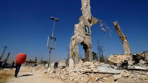 Ein Bild des syrischen Präsidenten Assad hängt über den Trümmern im Damaszener Vorort Al-Dukhaneya; Foto: Reuters/Omar Sanadiki