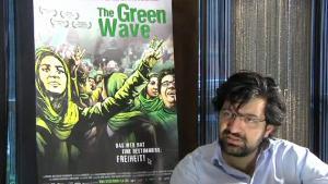 "Filmregisseur Ali Samadi Ahadi vor Filmplakat ""The Green Wave"""