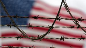 Symbolbild Camp Delta, Strafgefangenenlager Guantanamo: Stacheldraht vor US-Flagge; Foto: picture-alliance/AP Photo/B. Linsley