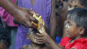 Rohingya-Flüchtlingskind erhält Nahrungsmittel im Hafen von Julok in Kuta Binje, Indonesien; Foto: Reuters/Beawiharta