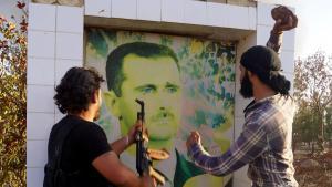 Syrische Oppositionskämpfer zerstören ein Poster des Regimeführers Bashar Al-Assad, Anfang Juni 2015. Foto: DW/ AA/ I. Hariri