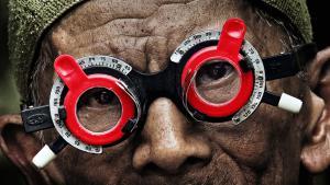 "Inong mit einer roten Optikerbrille auf Filmplakat ""The Look of Silence""; Foto: Dogfoof"