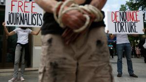 """Aktivisten von """"Reporter ohne Grenzen"""" demonstrieren im Juli 2012 auf den Champs Elysee in Paris gegen die Unterdrückung und Folter von Journalisten im Iran; Foto: EPA/IAN LANGSDON"""